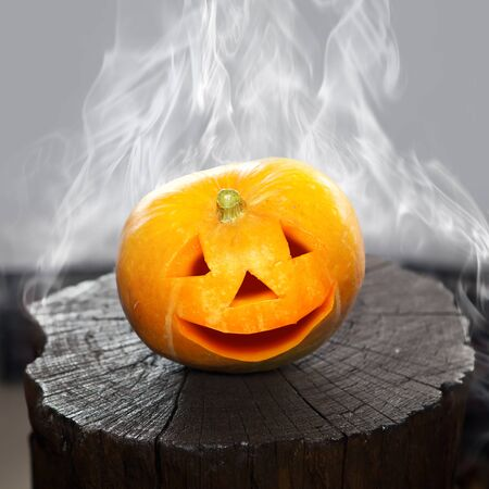 Pumpkin that laughs on a charred stub in smoke. Scenery for Halloween holiday.