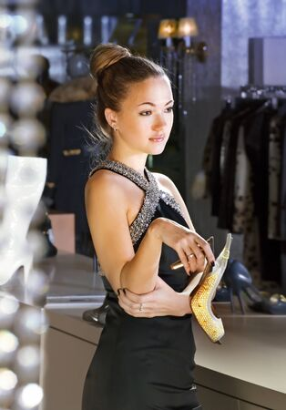 beautiful shop assistant with shoe in a boutique