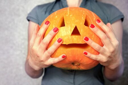 ripe pumpkin in hands of woman, useful vegetable for Halloween
