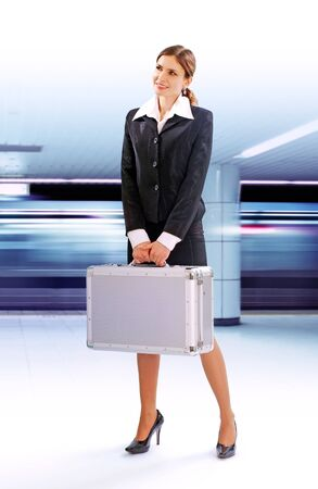 Businesswoman with a suitcase is waiting for a train in the underground. Business Trip.