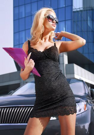 blonde pretty business woman looking away on street of city