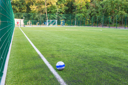 The ball lies on the green grass of the new football field. You can use this picture to popularize sports and healthy lifestyles. Stock Photo