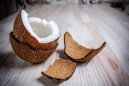 On the light surface of the table is one half the coconut in the hairy shell close up. Next to the coconut are the remains of a shaggy shell. Stock Photo