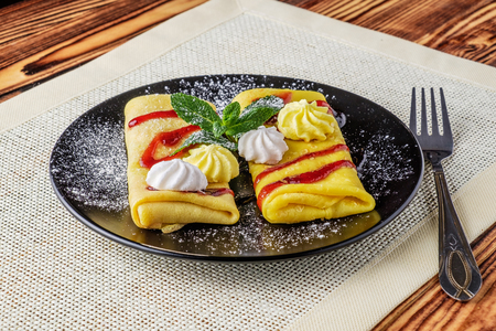 On the wooden table with pancakes. Pancakes are poured with jam, decorated with green mint leaves, sweet-stuffs and sprinkled with a sugar powder. Banque d'images