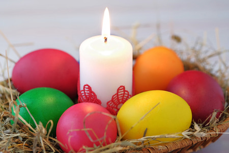 In the wicker basket lie Easter eggs and a burning candle. Close-up view. Foto de archivo