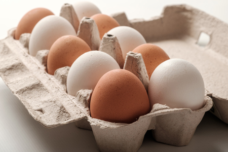 White and brown chicken eggs in a cardboard package.