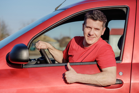Attractive white middle aged man sitting in red car, smiling and doing gesture thumb up.