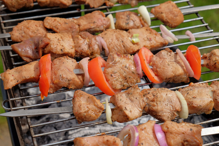 The row  of fried pieces of meat on skewers are roasted on a lgrill in the open air. The national dish of middle East. Closeup view. Stock Photo