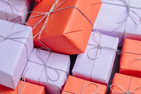 Festive presents wrapped in red and lilac paper and tied with si