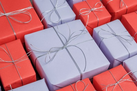 Lots of mix gifts wrapped in red and lilac paper and tied with silver twine. Selection presents for holidays. Top view.