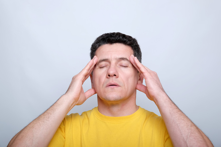 White middle-aged man with closed eyes touching his head with two hands. Headache and suffering concept