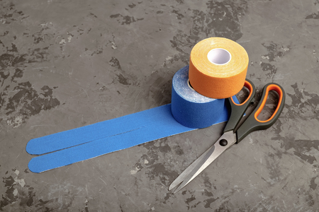 Scissors and two rolls special kinesiology tape for healing wrist pain, aches and tension.