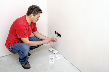 Electrician installs a new outlet indoors. The concept of construction, repair and renovation of buildings