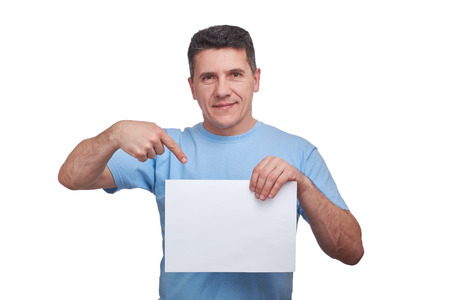 Handsome senior man with smiling face holding blank paper and making a gesture pointing his finger at him. Copy space, isolate on white