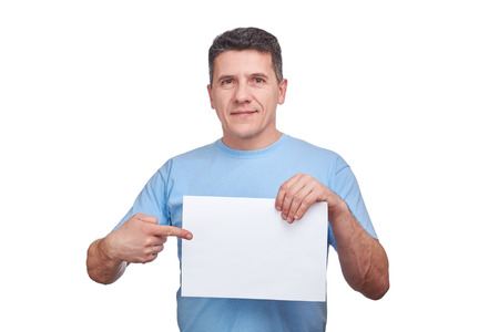 Handsome gray hair senior man with smiling face holding blank paper and making a gesture pointing his finger at him. Copy space, isolated on white Imagens - 120119649