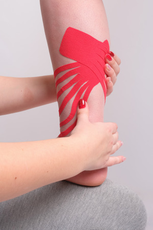 physiotherapists hands applying kinesio tape on the womans leg closeup. vertical view
