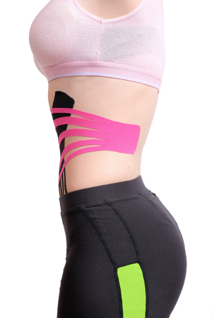 Crossed kinesio tape on abdomen of young girl, vertical orientation. isolated on white background Standard-Bild