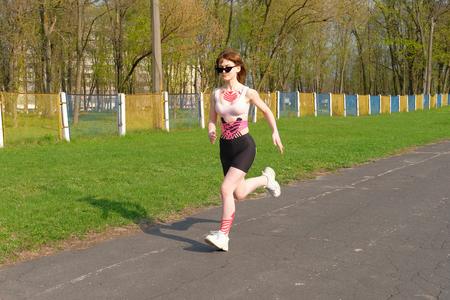 Mädchen mit Kinesio-Tape auf ihrem Körper, das im Frühlingspark auf verlorener Stadionbahn läuft.