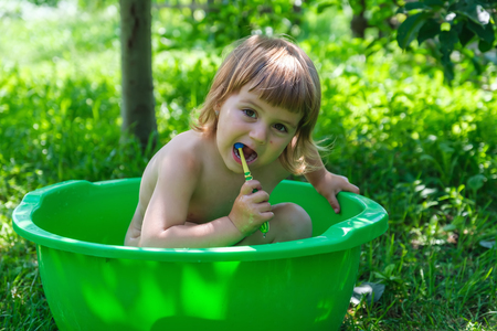 Cute white baby girl bathing and holding toothbrush in small bathtub over green background outdoors. concept of hygiene and oral health care for kids