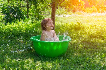 Outdoor baby bathing. smiling baby taking a bath and splashing in small bathtub outdoor. Hapiness and joy concept