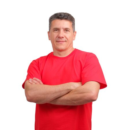 Portrait of a smiling positive man wearing red informal t-shirt with folded on chest hands, isolated on white background