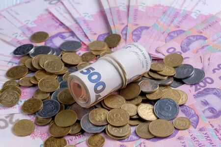 Ukrainian banknotes value of 200 and 500 hryvnia UAH and pile of coins. Closeup view Stock Photo