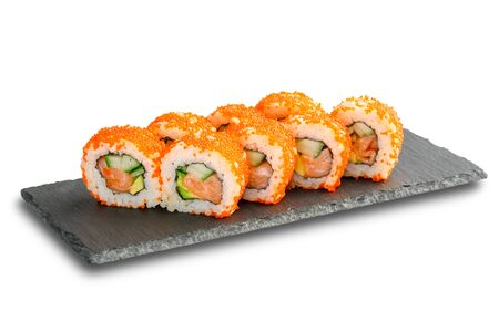Sushi Rolls with salmon, avocado, flying fish caviar and cucumber inside on black slate or stone shale surface isolated on white background. Stock Photo