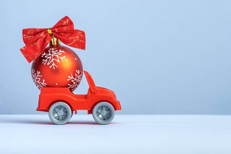 toy car with a Christmas ball on a light background. New Year, delivery concept.