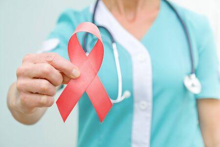 Rote Schleife für HIV-Krankheitsbewusstsein in der Hand des Arztes, Konzept des Welt-AIDS-Tages am 1. Dezember. Nahaufnahme