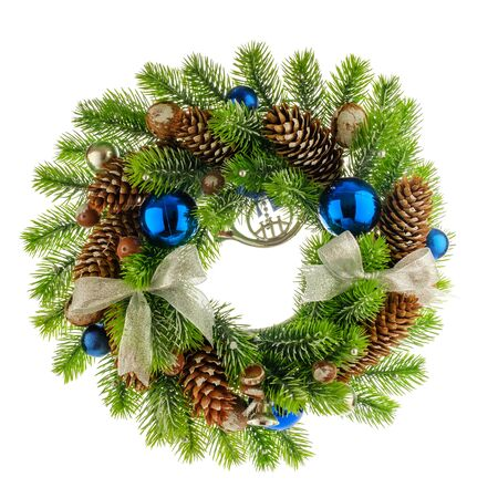 Christmas composition with Wreath made of christmas tree branches, acorns, walnuts and pine cones with blue bubbles on white background. Flat lay, top view