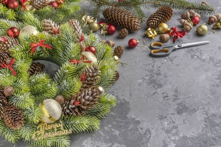 top view of Christmas wreath with fir, pine cones, balls , ribbons and acorns on concrete surface with copy space. Stock fotó