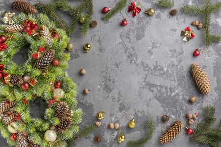 top view of two Christmas wreath with fir, pine cones, balls and ribbons on concrete surface with copy space.