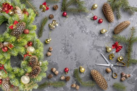 top view of Christmas wreath with fir, pine cones, balls and ribbons on concrete surface with copy space.