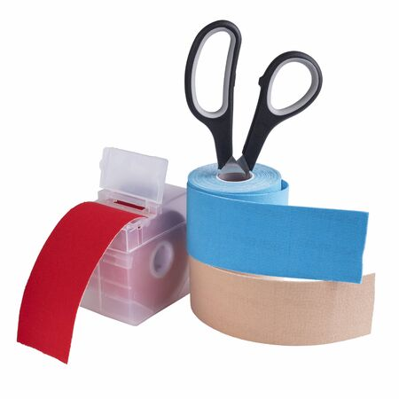 scissors, dispenser and rolls kinesiology tape for athletes isolated on white background. Kinesiology taping manipulate nerve receptors and reduces pain in muscles and speeds up the healing process