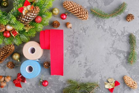 Christmas composition of wreath, fir, pine cones, balls, ribbons and rolls kinesiology tape for athletes on grey concrete background, top view, copy space Stock fotó