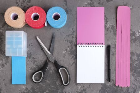 rolls kinesiology tape for athletes, scissors and notebook with pen on white background, top view. taping manipulate nerve receptors and reduces pain in muscles and speeds up the healing process