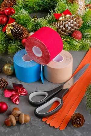 Christmas composition of wreath, fir, pine cones, balls, ribbons and stack of three rolls kinesiology tape for athletes and scissors on grey concrete background, vertical orientation