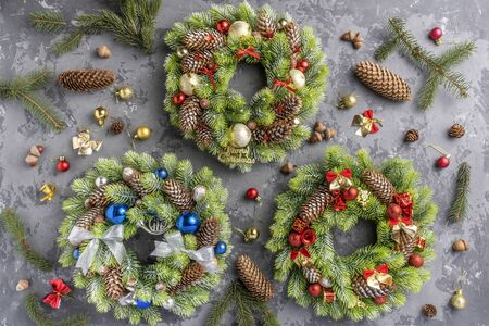 three Christmas wreath with fir, pine cones, balls , ribbons and acorns on concrete surface with copy space. top view