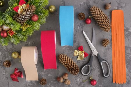 Christmas composition of wreath, fir, pine cones, balls, ribbons and rolls kinesiology tape for athletes and scissors on grey concrete background, top view.