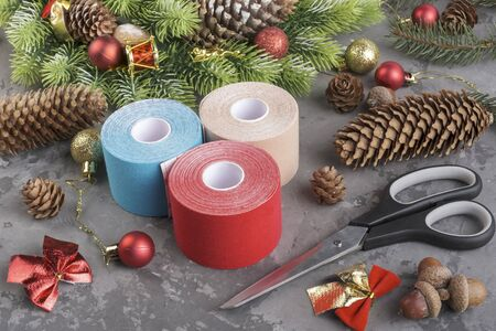 Christmas composition of wreath, fir, pine cones, balls, ribbons and stack rolls kinesiology tape for athletes and scissors on grey concrete background