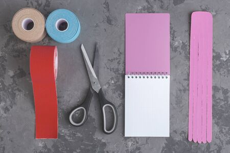 rolls kinesiology tape for athletes, scissors and notebook with pen on concrete background, top view. taping manipulate nerve receptors and reduces pain, speeds up the healing process, copy space