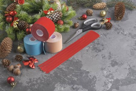 Christmas composition of wreath, fir, pine cones, balls, ribbons and stack of three rolls kinesiology tape for athletes and scissors with strip on grey concrete background Stock fotó