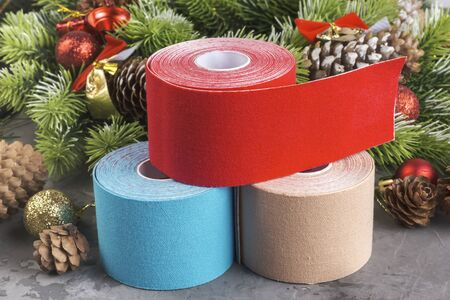 Christmas composition of wreath, fir, pine cones, balls, ribbons and stack rolls kinesiology tape for athletes on grey concrete background
