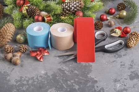 Christmas composition of wreath, fir, pine cones, balls, ribbons and stack rolls kinesiology tape for athletes and scissors on grey concrete background with copy space