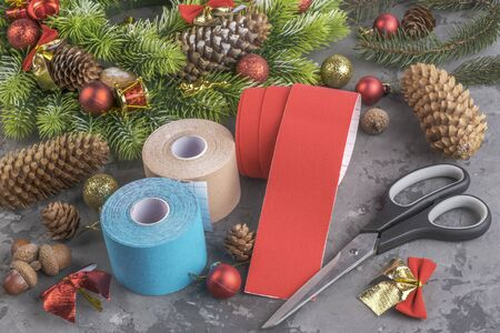 Christmas composition of stack rolls kinesiology tape for athletes, wreath, fir, pine cones, balls, ribbons and scissors on grey concrete background Stock fotó
