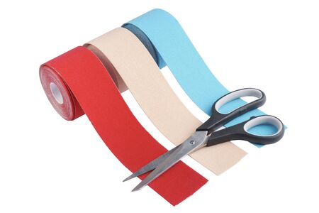three rolls kinesiology tape for athletes and scissors isolated on white background. Kinesiology taping manipulate nerve receptors and reduces pain in muscles and speeds up the healing process