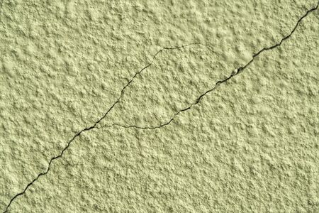 olive painted chipped plaster on the wall weathered with cracks and scratches. Stock fotó
