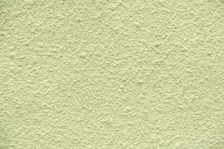 olive painted chipped plaster on the weathered wall