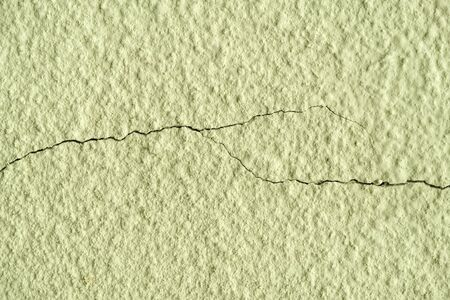 olive painted chipped plaster on the wall weathered with two horizontal cracks.