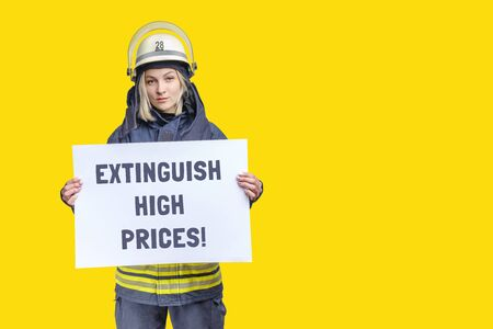 young beauty firefighter wearing uniform and helmet looking to the camera and holding paper sheet with inscription extinguish high prices in hands. isolated on yellow background